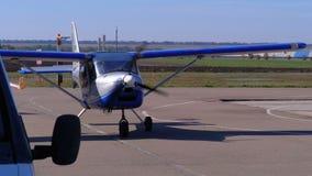 Pequeño aeroplano privado con un propulsor giratorio que se coloca en el estacionamiento de los aviones en un pequeño campo de av almacen de metraje de vídeo