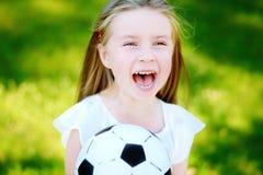 Pequeño aficionado al fútbol adorable que anima en día de verano caliente en el parque Imágenes de archivo libres de regalías