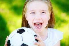 Pequeño aficionado al fútbol adorable que anima en día de verano caliente en el parque Foto de archivo