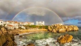 Pequeño arco iris doble imponente sobre una pequeña bahía Imagenes de archivo