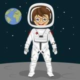 Pequeño astronauta del muchacho del empollón que se coloca en la superficie de la luna en el fondo de la tierra Fotografía de archivo libre de regalías