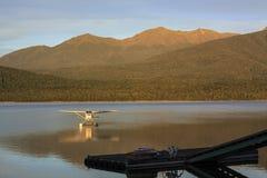 Pequeño avión en un lago. Salida del sol Foto de archivo