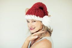 Pequeño ayudante de Santas Mujer mayor feliz hermosa con un sombrero de Papá Noel foto de archivo