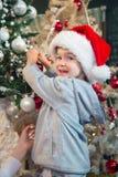 Pequeño ayudante de Santas que adorna el árbol de navidad Imágenes de archivo libres de regalías