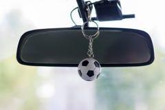 Pequeño balón de fútbol del llavero en el coche foto de archivo