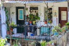 Pequeño balcón sucio viejo con muchas plantas en el distrito histórico de Affama en Lisboa, Portugal foto de archivo