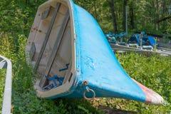 Pequeño barco azul abandonado en la hierba Foto de archivo