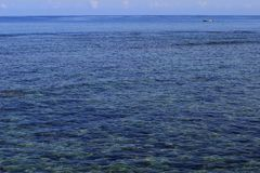 Pequeño barco blanco a la deriva en un mar azul grande Imagen de archivo