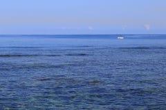 Pequeño barco blanco a la deriva en un mar azul grande Fotografía de archivo libre de regalías