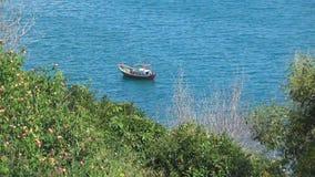 Pequeño barco de madera que oscila en las ondas La bahía es rodeada por el verdor El mar azul tiene una onda leve almacen de video