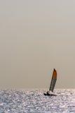 Pequeño barco de navegación del casco gemelo en el océano tranquilo Fotografía de archivo