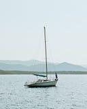 Pequeño barco de navegación en el mar tranquilo con las colinas Foto de archivo libre de regalías