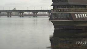 Pequeño barco de pesca anclado en el río al lado de un puente Naves en puerto almacen de video
