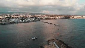Pequeño barco de pesca blanco con las velas azules del tejado en el mar abierto en la puesta del sol con la ciudad de vacaciones  almacen de metraje de vídeo