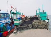 Pequeño barco de pesca con la red de pesca y equipo en el pueblo pesquero  Imágenes de archivo libres de regalías