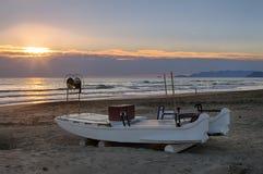 Pequeño barco de pesca de la fibra de vidrio en la playa en la puesta del sol foto de archivo