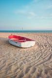Pequeño barco de pesca en la playa y el cielo azul Imagenes de archivo