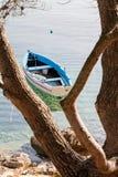 Pequeño barco de pesca de madera colorido que flota en el mar tranquilo Imagen de archivo