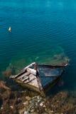 Pequeño barco de pesca mediterráneo viejo que se hunde dentro del embarcadero de Nea Artaki en Euboea - Nea Artaki, Grecia Imagen de archivo libre de regalías