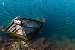 Pequeño barco de pesca mediterráneo viejo que se hunde dentro del embarcadero de Nea Artaki en Euboea - Nea Artaki, Grecia Imagen de archivo
