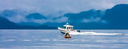 Pequeño barco de pesca pasajero por el barco de pesca grande fotos de archivo
