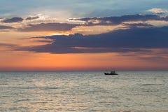 Pequeño barco de pesca sobre horizonte de la costa con el fondo de la puesta del sol Imagen de archivo libre de regalías