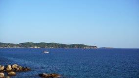 Pequeño barco de vela en el mar azul claro