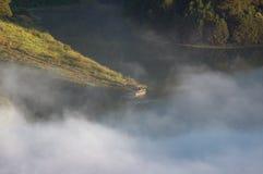 Pequeño barco del viaje en el lago en la mañana con niebla y la relajación fotografía de archivo