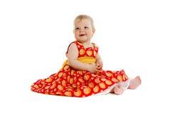 Pequeño bebé adorable en el vestido rojo que se sienta en piso Fotos de archivo