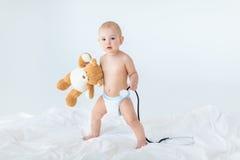 Pequeño bebé adorable que se coloca en cama y que sostiene el estetoscopio con el oso de peluche Fotografía de archivo libre de regalías