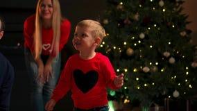 Pequeño bebé adorable que se divierte en una Nochebuena en casa, sonriendo y corriendo alrededor con un regalo de Navidad almacen de metraje de vídeo