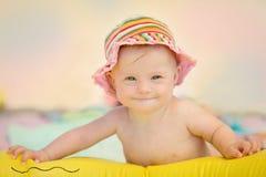 Pequeño bebé alegre con el síndrome de los plumones que juega en la piscina Imagen de archivo