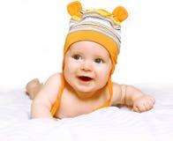 Pequeño bebé alegre en el arrastre del casquillo Fotos de archivo libres de regalías