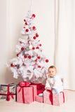 Pequeño bebé alegre que juega cerca del árbol de navidad Fotos de archivo libres de regalías