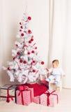 Pequeño bebé alegre que juega cerca del árbol de navidad Fotografía de archivo