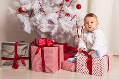 Pequeño bebé alegre que juega cerca del árbol de navidad Imagenes de archivo