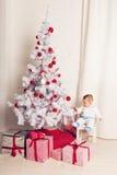 Pequeño bebé alegre que juega cerca del árbol de navidad Fotografía de archivo libre de regalías