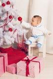 Pequeño bebé alegre que juega cerca del árbol de navidad Foto de archivo libre de regalías