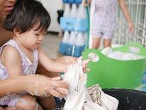 Pequeño bebé asiático que aprende lavar la ropa en casa imágenes de archivo libres de regalías