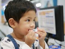 Pequeño bebé asiático que toma una paja hacia fuera de su paquete usando sus dientes foto de archivo libre de regalías
