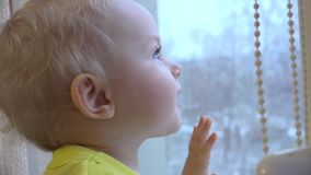 Pequeño bebé atractivo que mira hacia fuera la ventana 4K UltraHD, UHD almacen de video