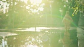 Pequeño bebé borroso en impermeable impermeable y los paseos de goma de las botas de lluvia en charcos después de la lluvia metrajes