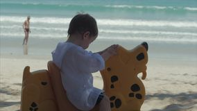 Pequeño bebé caucásico lindo 2-3 años del niño, bebé que juega con Sunny Summer Day Outdoors en fondo del océano almacen de metraje de vídeo