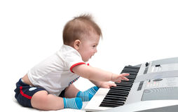 Pequeño bebé con el piano eléctrico Imagen de archivo