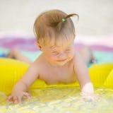 pequeño bebé con el síndrome de los plumones que juega en la piscina Fotos de archivo