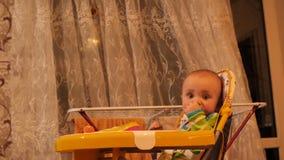 Pequeño bebé con el soother en la boca que se sienta en silla, mirando la cámara y 4K gritador MES lento metrajes