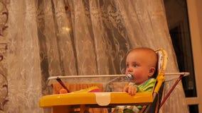 Pequeño bebé con el soother en la boca que se sienta en la silla y 4K gritador MES lento metrajes