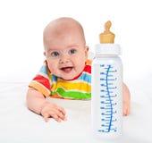 Pequeño bebé con la botella de leche. Foto de archivo