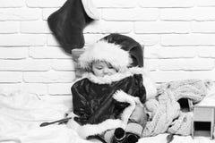 Pequeño bebé con la cara curiosa adorable en suéter rojo con el maniquí en la media del sombrero y de la Navidad o de Navidad del imágenes de archivo libres de regalías