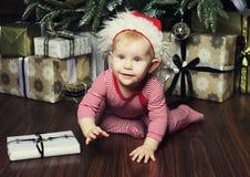 Pequeño bebé con la Navidad de adornamiento cercana tr de la caja de regalo Imágenes de archivo libres de regalías